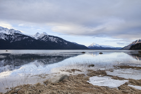 Dark clouds over the Chilkat Estuary near Haines, Alaska with an incoming tide at sunset in winter. Stock Photo