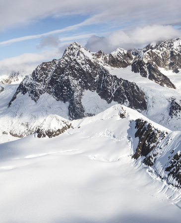 View from a small plane flying over the magnificent mountains of Southeast Alaska with snow.