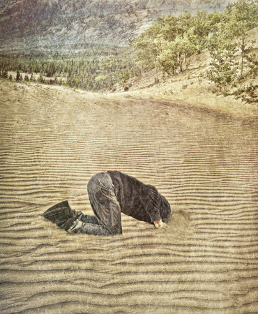 Concept shot of a man with his head in the sand with textures added.