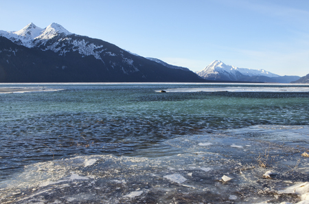 High tide at the Chilkat Estuary near Haines, Alaska in winter with ice forming and ice covered with water on a sunny day.