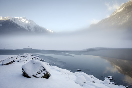 Fog layer over Chilkoot lake near Haines, Alaska in winter with snow and ice forming and the mountains reflected in open water.