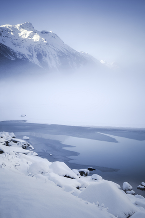 Fog over Chilkoot lake in winter with melting ice and snow.