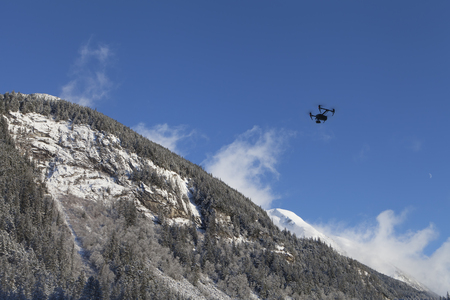 Black drone in the sky over mountains in winter dusted with snow on a sunny day. Stock Photo