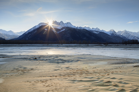 Sun going down behind Cathedral Peaks near the Chilkat river in Southeast Alaska on a windy cold winter day.