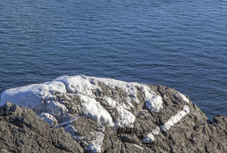 Rocks coated with ice from ocean spray in winter on the coast of Southeast Alaska