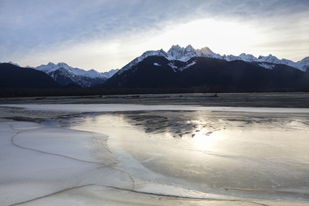 Sunset near the Chilkat River in Southeast Alaska with mountains reflected in ice.