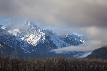 Fog and low clouds clearing to reveal the Chilkat Mountains near Haines, Alaska.