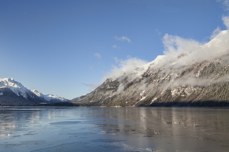 Fog clearning on a sunny winter day in the Lutak Inlet near Haines Alaska. Stock Photo