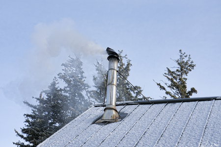 Smoke pouring out of a stove pipe on a metal roof from a wood fire on a winter day.