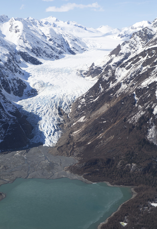 Aerial photo showing the Glacier near Glacier Point in Southeast Alaska receding with a small lake below the moraine. Stock Photo