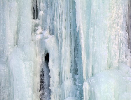 Patterns and color in a frozen waterfall on an Alaskan cliff in winter.