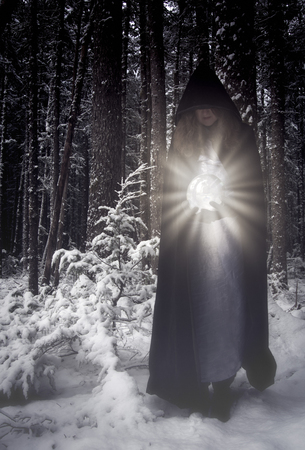 Woman in a long hooded cape in a winter forest holding a glowing crystal ball.