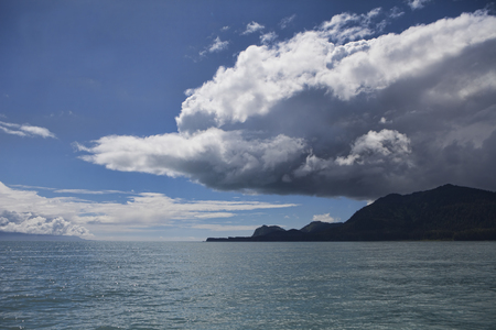 Dark storm cloud forming over an island in Cross Sound in Southeast Alaska in summer as seen from a boat. Stock Photo