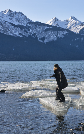 Man on an ice chunk in a surfing position in the Chilkat Inlet in Southeast Alaska in winter.