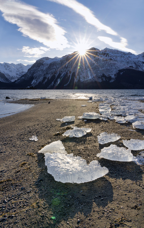 Sunburst as the sun sets over the Chilkat mountains in Southeast Alaska near Haines with ice chunks on the beach in winter. Stock Photo
