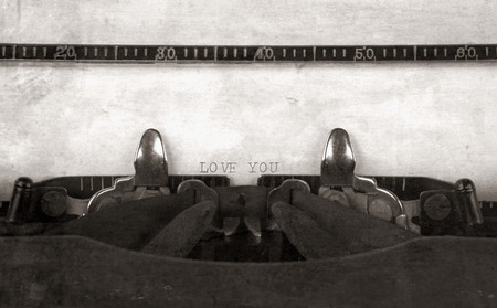 LOVE YOU typed on a vintage antique typewriter with an old fashioned look in monochrome.