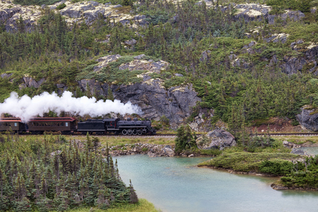 Steam train heading from Canada to White Pass in Alaska in summer.