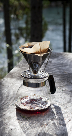 Making coffee with a drip filter holder on a rustic table near a river in summer.