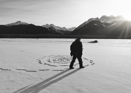 Man making a sprial in the snow as the sun sets on the frozen Chilkat river near Haines, Alaska. Stock Photo