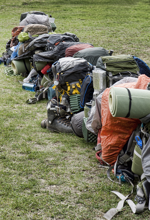 Row of backpacks and gear ready for a group hike on the Chilkoot Trail in Southeast Alaska near Skagway in summer. Stock Photo