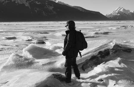 Man dressed in warm winter clothes near a frozen river in Alaska with huge ice chunks in black and white. Stock Photo