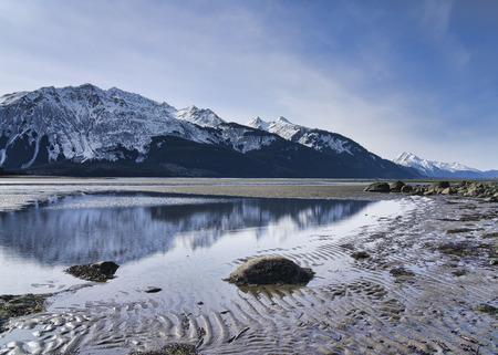 Chilkat mountains reflected in water in the tidal estuary of the Chilkat inlet in winter. Stock Photo