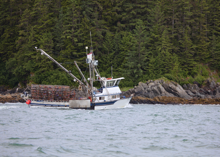 Crab fishing boat near the shore of the Lynn Canal in Southeast Alaska loaded with empty crab pots.