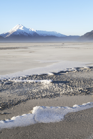 Sandy silt covering a frozen river on a sunny day in Southeast Alaska near Haines.