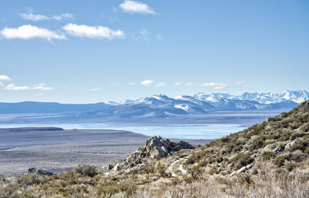 Mono Lake from above with the White Mountains still covered with snow and an old jeep trail in the foreground.