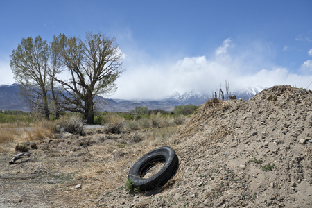 An old abandoned tire by a pile of dirt near Bishop California with trees and mountains in the background.