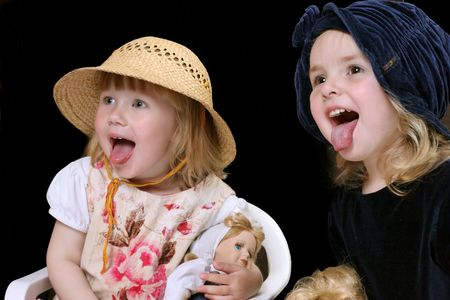 two happy funy little girls in hats showing tongues