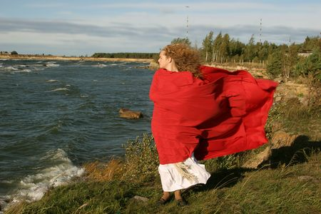 lady in red on windy day near  the sea photo