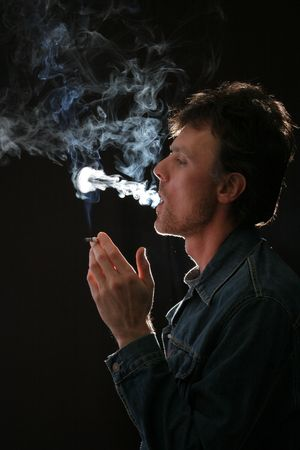 a man with cigarette in dark studio  photo