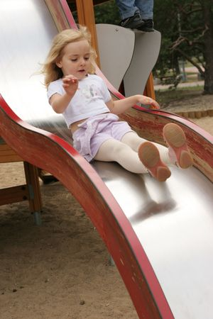 girl on the slide - outdoor activity in preschool Stock Photo