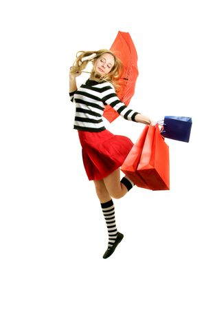 happy teenager girls  with red umbrella and shopping bags  jumping - over white\r Standard-Bild