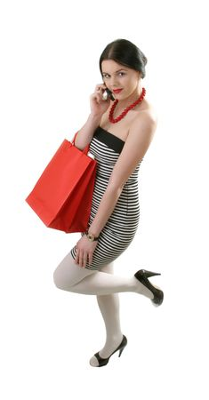 beautiful young woman with shopping bag talking by phone photo