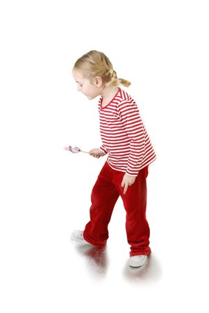 cute little girl with lollypop walking ower white Stock Photo - 2743270