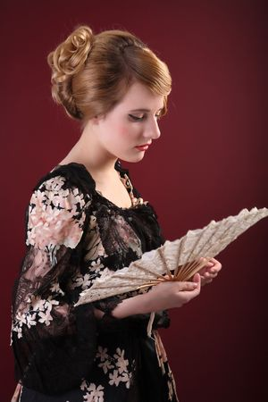 pretty young lady  in old time ball dress with fan  in  style of the end of XIX century Stock Photo