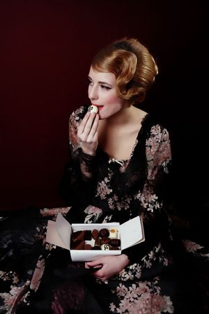 Pretty young lady in old time ball dress  eating white Chocolate  with letter N