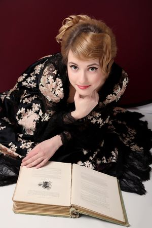 dressups:  pretty young lady  in old time (XIX century)  dress reading book published in  XIX century Stock Photo
