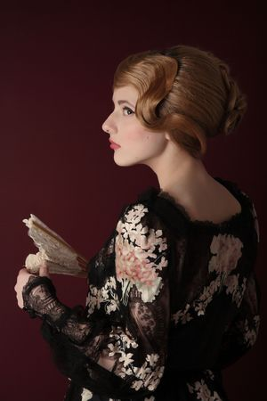 pretty young lady  in old time ball dress with fan