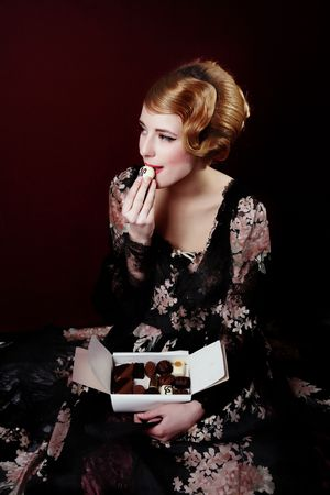 dressups: Pretty young lady in old time ball dress  eating white Chocolate  with letter N