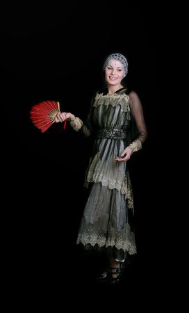 the emancipation: Standing girl with a red fan dress in  style of the beginning of XX century Stock Photo