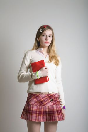 Sweet teenager school girl in pink mini skirt with red book photo