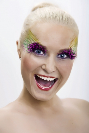 a funy portrait of a young girl with crazy face and make-up photo