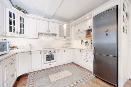 tiled stove: white elegant wooden kitchen with white carpet