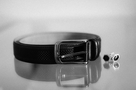 Belt and cufflinks on a glass