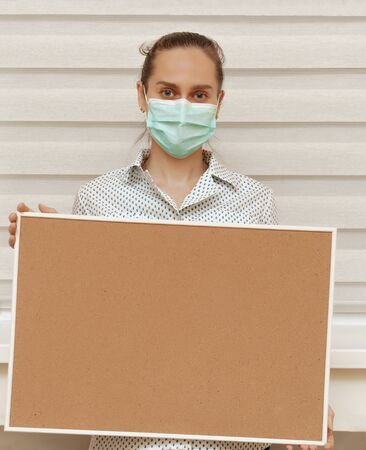 A young woman in a mask holds an empty cork board in her hands, standing on a white background. Copy space on whiteboard for image or message. Young woman. Concept of paying attention to your promise