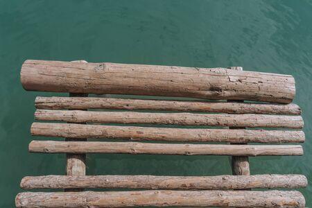 wooden bridge of bars on the lake close-up. Фото со стока