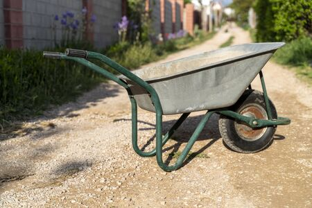 An old garden car stands on the road of a holiday village. The concept of work in the country, gardening.